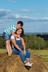 Little brother embracing his older sister sitting on a haystack