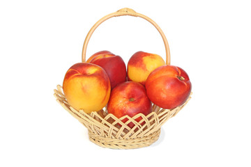 Nectarines in wicker basket isolated on white