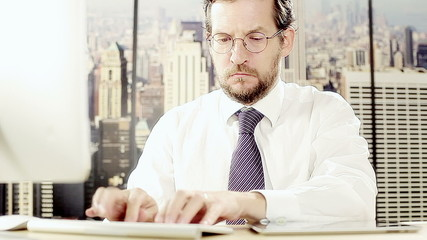 Man working pc and tablet in office in city with skyscrapers