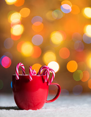 mug with candy canes in snow with bokeh backgroundwith copyspace