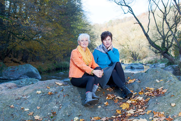 Two women sitting on a rock in the river