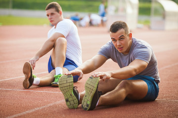 Young athletes sitting on a running track stretching