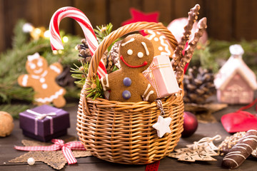 Basket of various Christmas treats, gingerbread man on the table