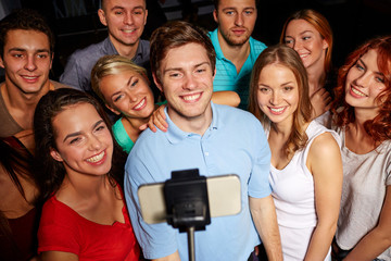 friends with smartphone taking selfie in club