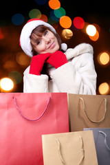 Young smile woman in Santa's cap and red gloves with bags