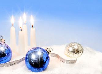 vier Adventskerzen und Weihnachtskugeln im Schnee