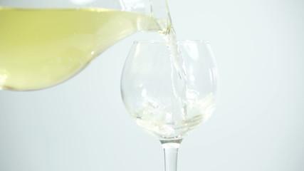 Pouring white wine on white background