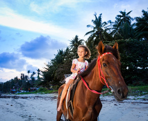 Portrait of an cute little girl riding horses at sunset