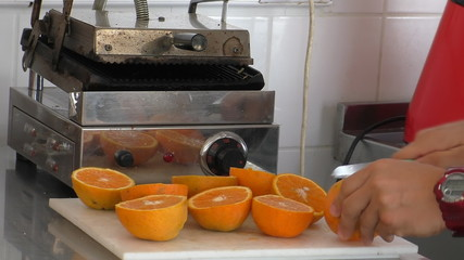 Cook or barman cutting oranges for juice