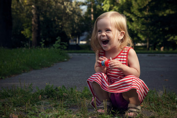 Little Blond Girl Enjoying Blowing Bubbles in the Summer Park