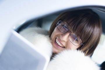 Woman in white coat working on laptop in car