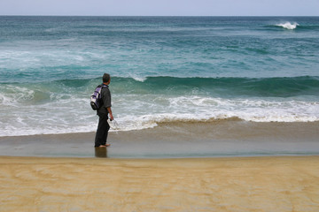 Man standing on a beach and looking at the ocean