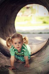 Little Girl with Pigtails Discovering First Steps in Tunnel