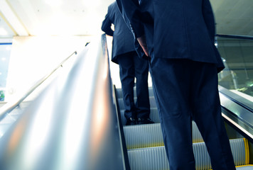 businessman going up the escalator