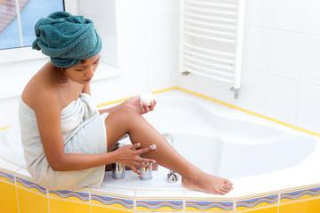 young woman creams her leg
