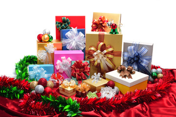 Gifts box and christmas balls on red cloth isolated on white