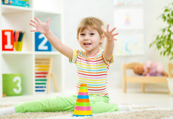 cheerful kid girl playing at children room