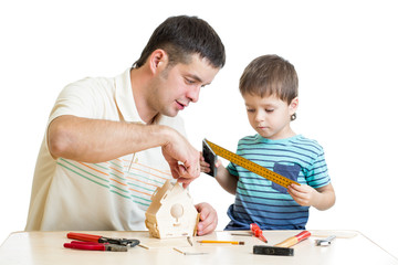 Father and son kid making wooden nesting box