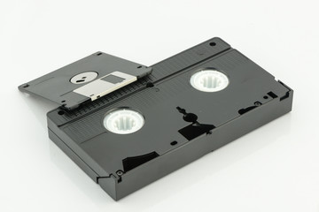 "videotape and 3.5"" diskette on white background"