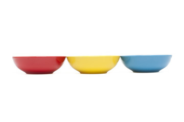 Row with three colorful bowls isolated over white