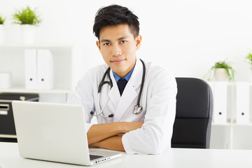young doctor working with laptop in office
