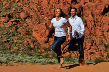 Young Couple Running on a Sand Dune