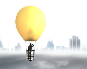 businessman in brightly yellow lamp hot air balloon flying