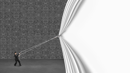 businessman pulling down white curtain covering old dark brick w