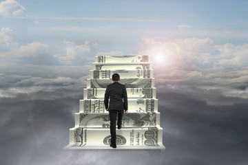 businessman climb on money stairs with natural sunlight cloudsca