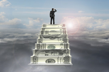 businessman on top of money stairs looking at sunlight cloudscap