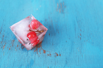 Ice cubes with red currant, on wooden background
