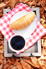 Cup of tasty hot drink and fresh croissant