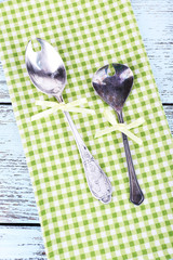 Metal spoons on green checkered napkin on wooden background