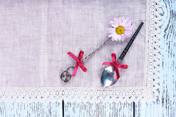 Spoons on lace napkin on wooden background
