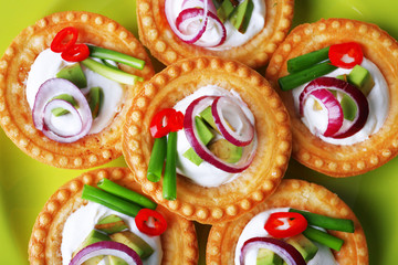 Tartlets with greens and vegetables with sauce on plate