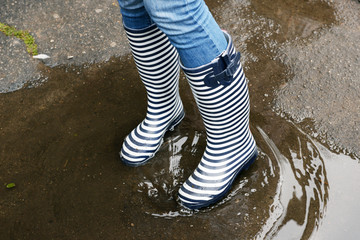 Girl in rubber boots outdoors in autumn