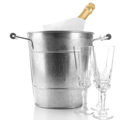 Bottle of champagne in metal ice bucket and two glasses