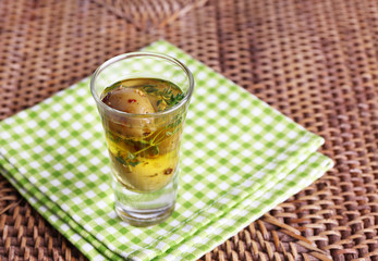 Green olives in oil with spices and rosemary in glass on table