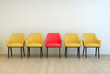 Yellow chairs aligned with a red one in the middle - 73400564