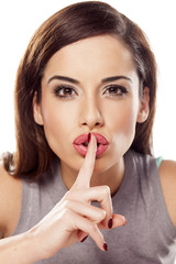 pretty girl holding a finger on her lips