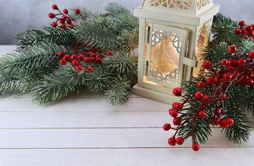 Lantern for candle with berries and conifer on white planks