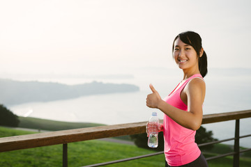 Positive sporty woman doing thumbs up gesture