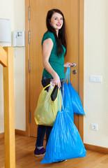 Happy  woman near door with garbage