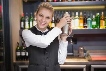 Pretty blonde waitress shaking cocktail