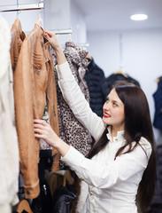 Cute woman choosing jacket at clothing store