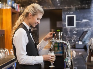 Barmaid pulling a glass of beer