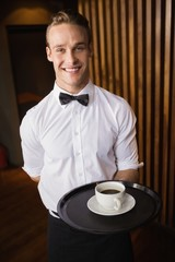 Waiter holding tray with coffee cup