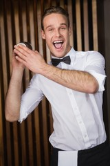 Happy waiter shaking drink in cocktail shaker