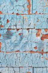 Peeling blue paint on wooden planks with selective focus