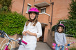 Couple of young girls portrait wearing helmet with bike outdoors